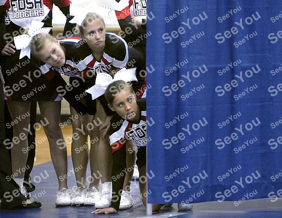 -Messenger photo by Hans Madsen<br /> <br /> Fort Dodge Senior High School cheerleaders Stephanie Dunbar, left, Taylor Hancock and Emma Dornath, right, peek around the corner from the warmup area to watch a squad ahead of them perform their routine Saturday morning at the Triton Cheerleading Challange held at Iowa Central Community College.