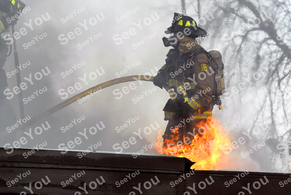 -Messenger photo by Hans Madsen <br /> <br /> Fort Dodge firefighter      prepares to spray water through a hole cut into the roof of the New Star Mini Mart Thursday afternoon as they battle a blaze in the rear of the building.