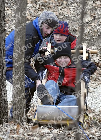"-Messenger photo by Hans Madsen<br /> <br /> Members of Humboldt's Troop 108 use their Klondike sled to get Zach Collins, 13, back to safety after he ""broke"" his leg. Robert Monson, 13, at left, along with Jared Knapp, 12, push. Another victim, Aaron Diesburg, 12, is actually under Collins."