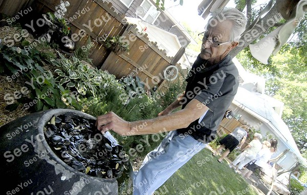 -Messenger photo by Hans Madsen<br /> <br /> Steve Fortney moves a rock out of the way from a fountain in his backyard Saturday morning during the 11th annual Fort Dodge Federal Garden Club garden tour. Fortney said that one of the local squirrels moves the rocks when he frolics in the water.