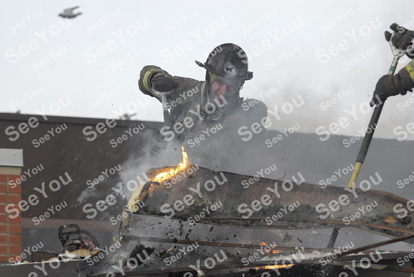 -Messenger photo by Hans Madsen<br /> <br /> Fort Dodge firefighter      sends up a shower of debris as he works on tearing through the roof of the New Star Mini Mart Thursday afternoon while battling a fire in the rear of the building.