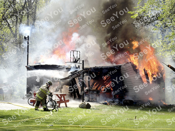 -Messenger photo by Emilie Nelson <br /> <br /> A Fort Dodge firefighter moves a bicycle from the area of a burning garage at 1621 14th Ave. SW Wednesday afternoon. The garage was fully engulfed in flames when firefighters arrived around 12:15 p.m. According to firefighters, the blaze was  started by an unattended wood burner. The property is owned by Joe Harvey, and rented by Ryan Andrews. The garage was considered a total loss.