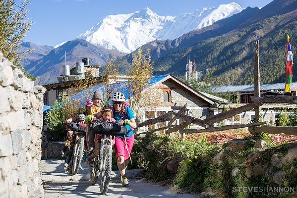 Miranda Murphy giving the local kids a ride in Manang, Nepal.  This was near the end of our third day full day on the bikes.  From our start at Besi Sahar in near tropical temperatures (and humidity!) we had climbed from 800 metres above sea level to over 3500 metres.  The landscape had changed dramatically during the past few days and we were excited to finally see the snow-capped Himalayan summits of the Annapurna range.  Riding through the gated entrance to the town we were greeted by enthusiastic children eager to try out our bikes.  I quickly ditched my bike at the tea house we were staying at, then ran after Miranda and Kathryn.  One of my goals of the trip was to capture some images of the locals and I'm really stoked on how this shot of Miranda with the kids turned out.