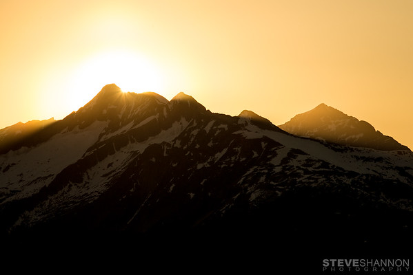 The sun sets over Frenchman's Cap, Hat Peak and Cat Peak in the Monashee Mountains north of Revelstoke, British Columbia.