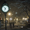 People walk the streets of Revelstoke during a winter snowstorm at night.