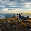 The sun sets over a motorcycle on Sproat Mountain with Arrow Lake in the background in the Selkirk mountains south of Revelstoke, British Columbia.