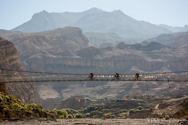 Bikepackers cross a bridge near Chhusang in the Mustang region of Nepal.
