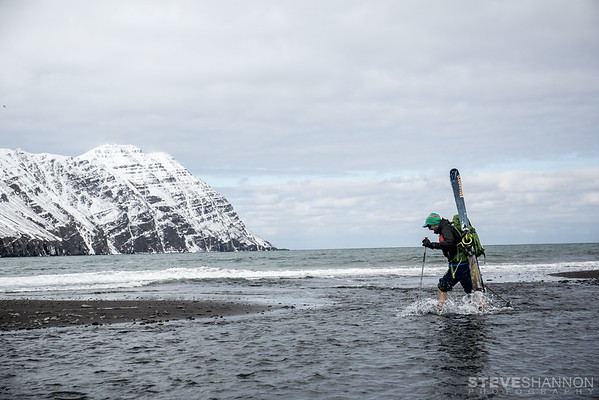 Photographer Steve Shannon crossing a small stream while ski traversing from Olafsfjordur to Siglufjordur on Iceland's Troll Peninsula.  Photo taken by Robert Stoeckel.