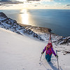 Emelie Stenberg bootpacking up a couloir on Iceland's Troll Peninsula as the sun sets over the Greenland Sea.
