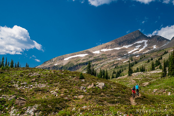 Mountain bikers ascend towards Caribou Pass under the shadow of Mount Fosthall.