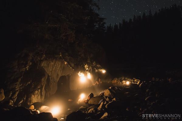 A couple enjoys the natural hotsprings along Halfway river near Nakusp, British Columbia under a starry sky.<br /> Models: Jessica Nilsen & Tyler Bradbury<br /> Location: Nakusp, BC