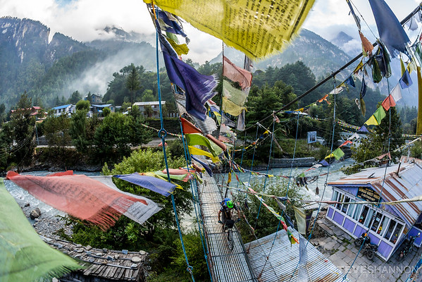 Todd Weselake crosses a bridge in Chame, Nepal.  Chame is a popular stop along the Annapurna trekking circuit.  With its rich culture and views of Himalayan peaks, it is the gateway to the Manang district.