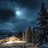 A cozy backcountry lodge nestled in the snowy Selkirk Mountains during a cold winter night.  <br /> Location: Selkirk Wilderness Skiing, Meadow Creek, British Columbia