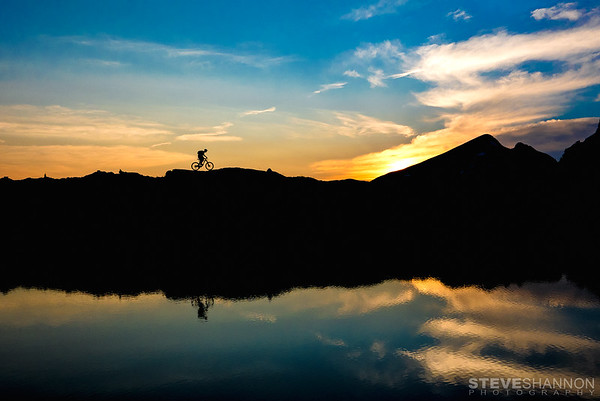 A mountain biker is reflected in the waters of Sol Lake at sunset.