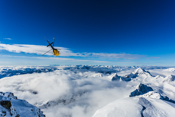 A helicopter flies over the Goat Range of the Selkirk Mountains after dropping off heli skiers on Mount Brennan near Kaslo, British Columbia.