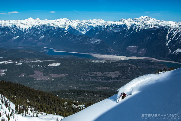 Joe Schwartz at Selkirk Wilderness Skiing.  The Lardeau Valley, Duncan Lake and the Purcell Mountains in the background.