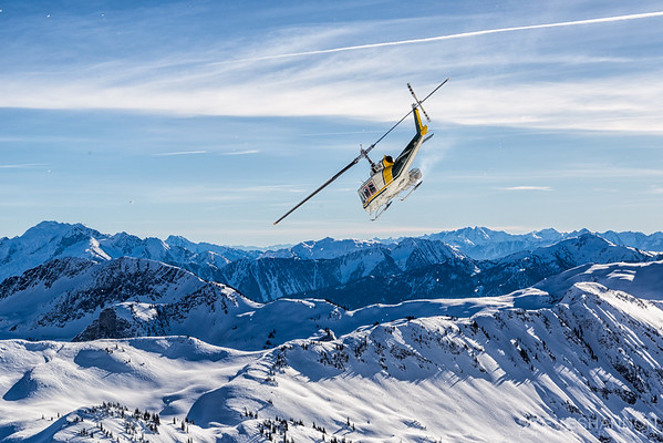 A helicopter flies over the Selkirk Mountains during a heli-ski day with Selkirk Tangiers Heli Skiing near Revelstoke, British Columbia.