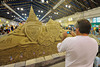 A man photographing the completed 9/11 heroes tribute sand sculpture in the Center of Progress bulding at The Great New York State Fair in Syracuse, New York.