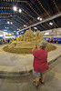 A woman photographing the completed 9/11 heroes tribute sand sculpture in the Center of Progress bulding at The Great New York State Fair in Syracuse, New York.