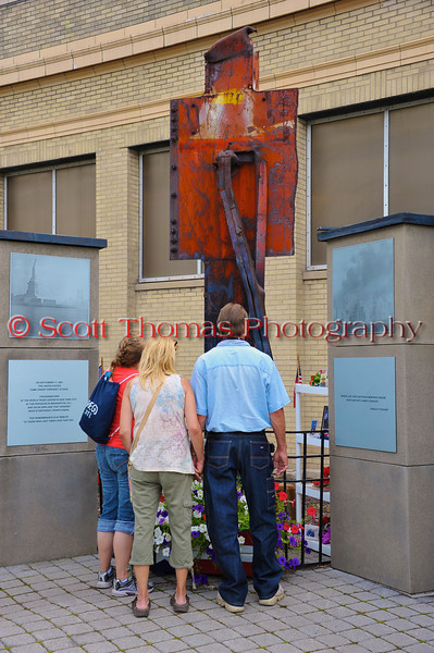 People standing before the 9/11 Memorial in front of the Horticulture building at The Great New York State Fair in Syracuse, New York.