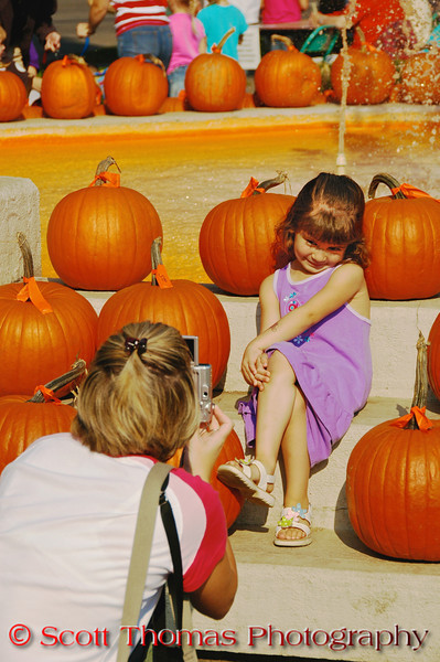 A girl posing for her mother among the pumpkins surrounding the orange colored water fountain during the Great Cortland Pumpkinfest in Cortland, New York. {For Non-Commercial Editorial Use Only]