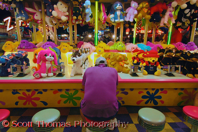 A lone player sitting on a stool at a game booth at night on the Midway of the New York State Fair in Syracuse.  [For Non-Commercial Editorial Use Only]