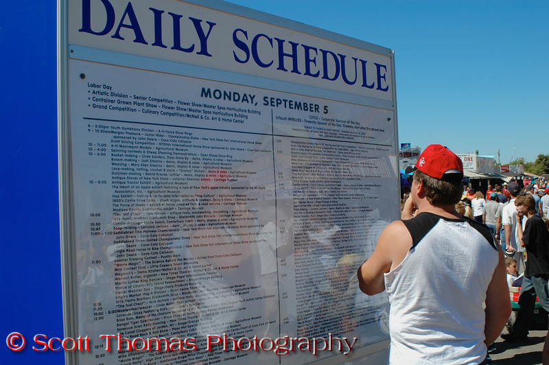 A New York State Fair goer trying to decide which event to attend during a day at the Fair in Syracuse, New York.