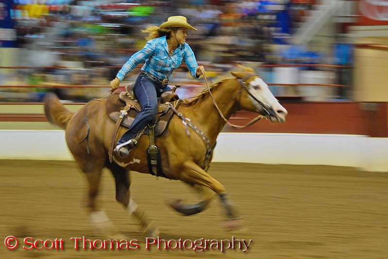 Rider and horse competing in the New York State Barrel Racing Championship in the Coliseum at the Great New York State Fair in Syracuse, New York.