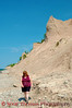 A woman walks along the rocky beach under the  pinnacles and cliffs of Chimney Bluffs State Park near Sodus, New York.
