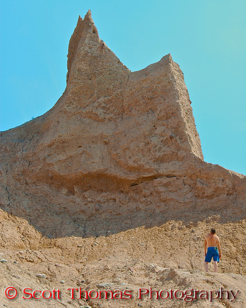 A hiker looks up at one of the large rock pinnacles in the Chimney Bluffs State Park near Sodus, New York.