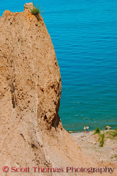 Visitors walk past a large rock pinnacle in Chimney Bluffs State Park near Sodus, New York.