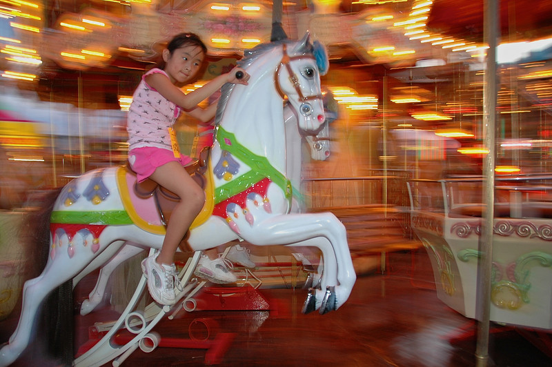 A girl riding a carousel horse at night on the Midway at the New York State Fair in Syracuse.  [For Non-Commercial Editorial Use Only]