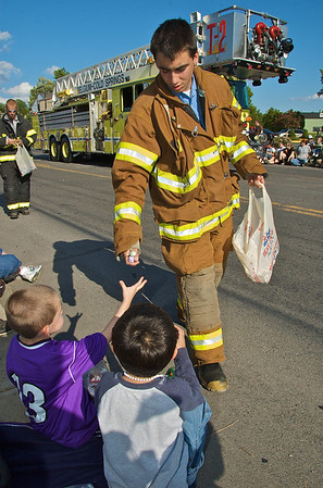 A volunteer fireman from teh Belguim Cold Springs Fire Department hands out candy to parade watchers during the Baldwinsville Memorial Day Parade on Saturday, May 30, 2009.