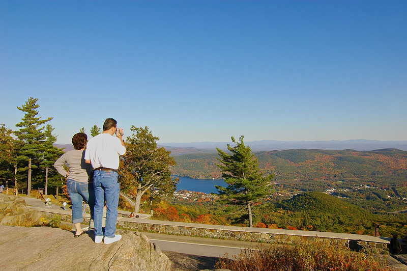 Tourists photograph the view from the summit of Prospect Mountain overlooking Lake George, New York.
