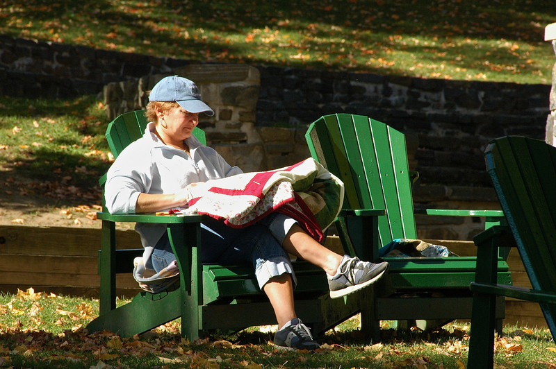 Sitting in the many Adirondack chairs found in Shepard Park, someone works on a quilt in Lake George, New York.