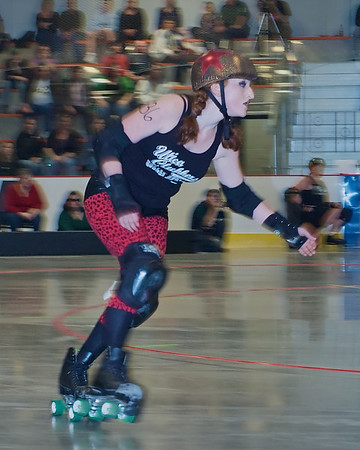 A Jammer, a skater with the star on her helmet, eyes the gaggle of blockers she must get through to score points for her team, the Utica Clubbers.<br /> <br /> Women's CNY Roller Derby Bout in the JFK Civic Arena in Rome, New York.