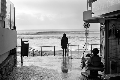 Lady in winter clothing watching the surf, surrounded by shops and Noddys play car. Estoril, Portugal