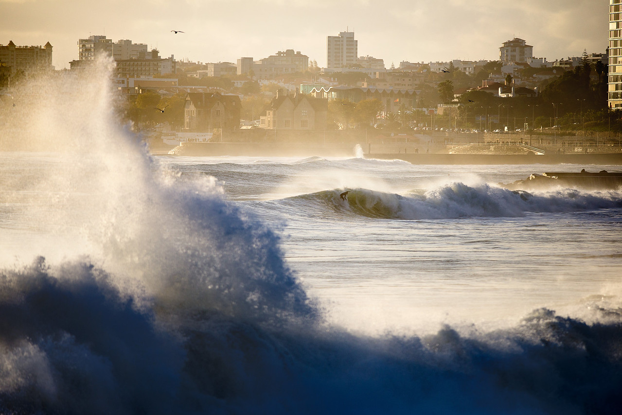 Surfer framed by wave and city buildings,  Estoril, Portugal, 2014