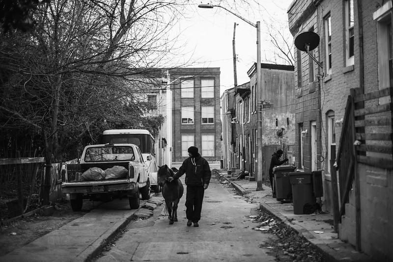 Baltimore -- Gready walks Bey down South Carlton Street toward a small lot on Nov. 28, 2018.