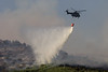 SA Air Force helicopter drops water on bush fire