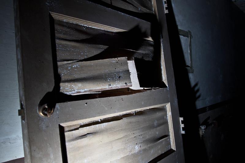 A broken, scattered door standing in the middle of a room.