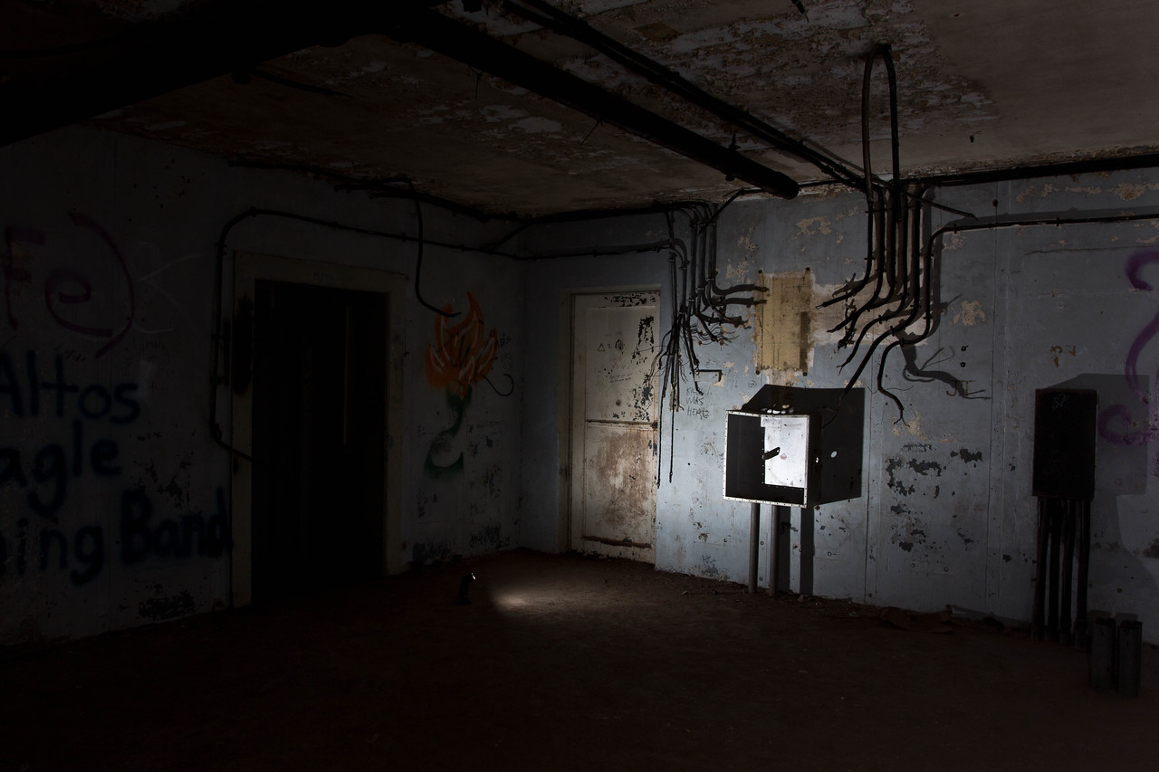 Deep in the bunker. The cables look like mystic hands going to grab you. The paint is falling off and it is pitch dark.