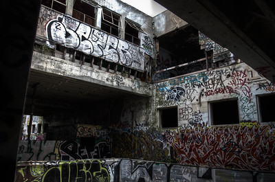 The courtyard of the 2 stories building. There are spray cans everywhere and almost no wall is untouched.