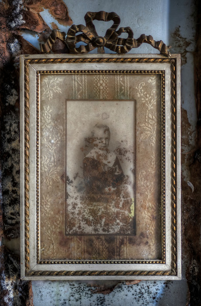 The Forgotten - Inside an abandoned castle I found this photo of a young boy still present in his old bedroom. The mold on the wall has already spread to the photo itself.
