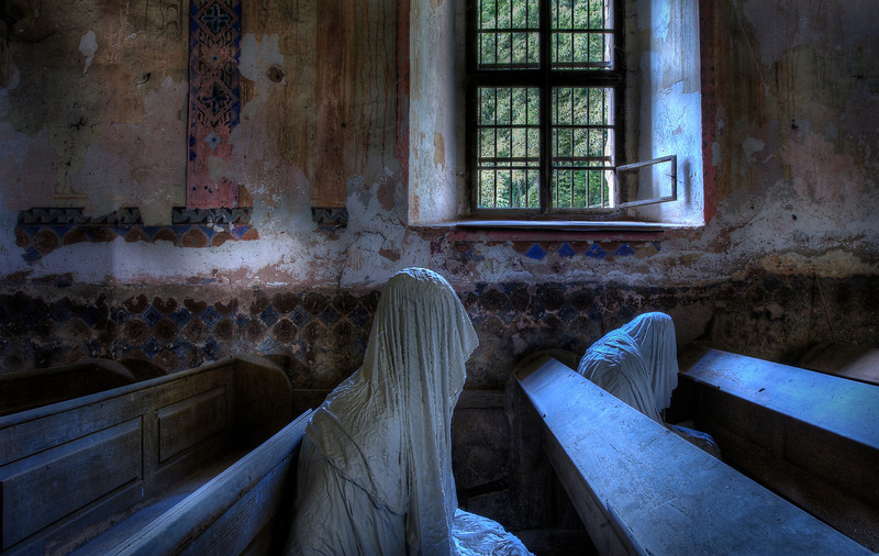 "The Last Rites - In 2012 during an awesome tour our next stop was a possible abandoned church. But when we peeked through the windows we got a lot more than what we bargained for. In the pews were 9 ""ghosts"" all dressed in wrinkly cloths. At least 5 times a week I get the same question ; What was underneath ?? Well, I do not know. We never looked. I suppose some sort of framing. Nevertheless a very creepy but memorable experience !"