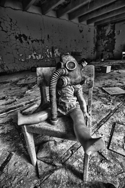 Deafening Silence - Chernobyl Exclusion Zone 2010. A doll with a gasmask left behind in an old kindergarten in Pripyat. Probably a setup but it's a great example of the 2 things you see most scattered around. The place is littered with children's toys, little shoes and gasmasks. It's a sad thing to see. Is this the world we created ?
