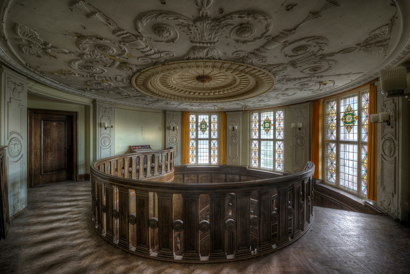 Round - Decorated ceiling above a spiral staircase in an abandoned house. No vandalism here, no graffiti and the windows still in one piece.