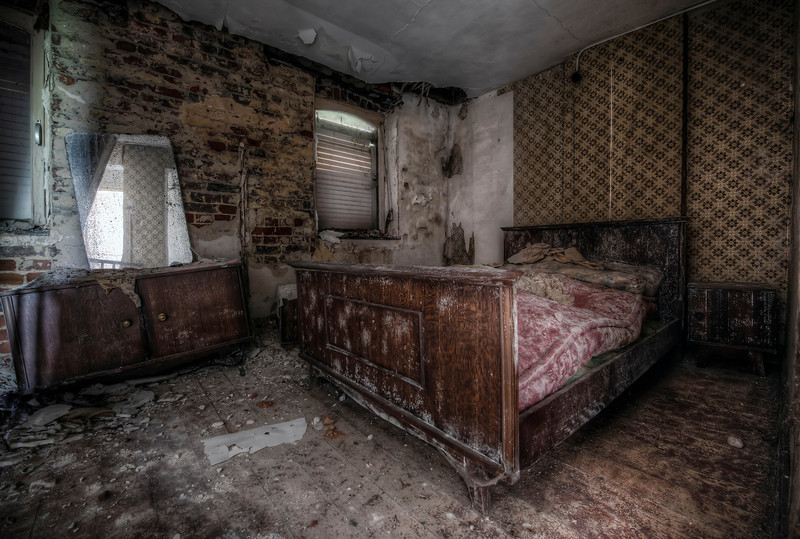 Don't Let The Bed Bugs Bite - Extremely decayed bedroom in a small abandoned farmhouse. Floors have already started to collapse and it won't take very long before the whole place will crumble.