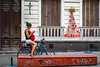 A young lady with  bicycle checking her cell phone in Montevideo, Uruguay, South America.