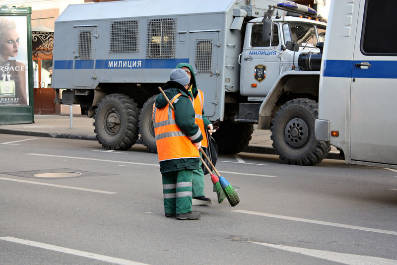 Street sweepers following behind the crowd.